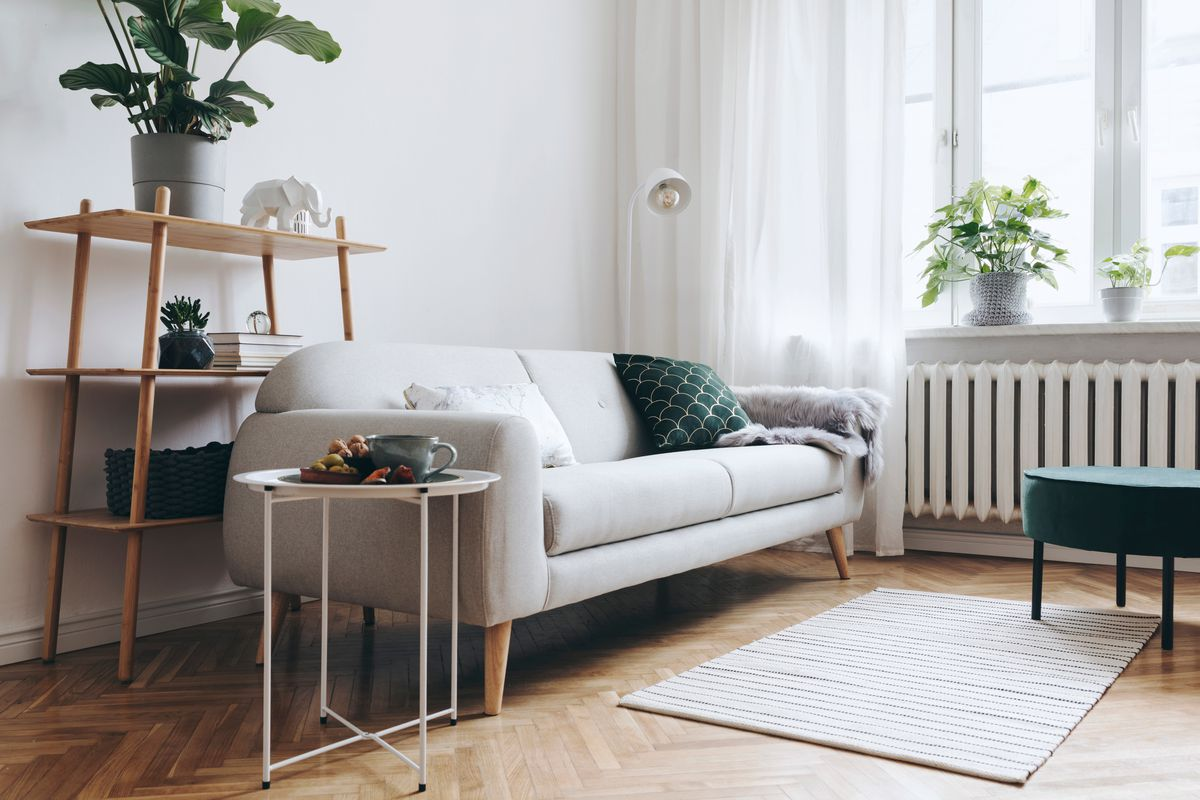 A living room apartment features a white couch with open shelving behind it, a white spindly side table, and windows with breezy white curtains on the right.