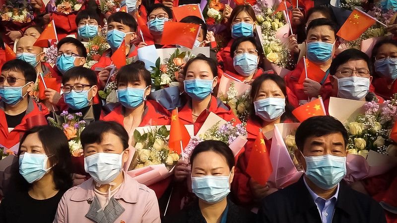 A crowd of Chinese people wearing masks and holding the Chinese flag.