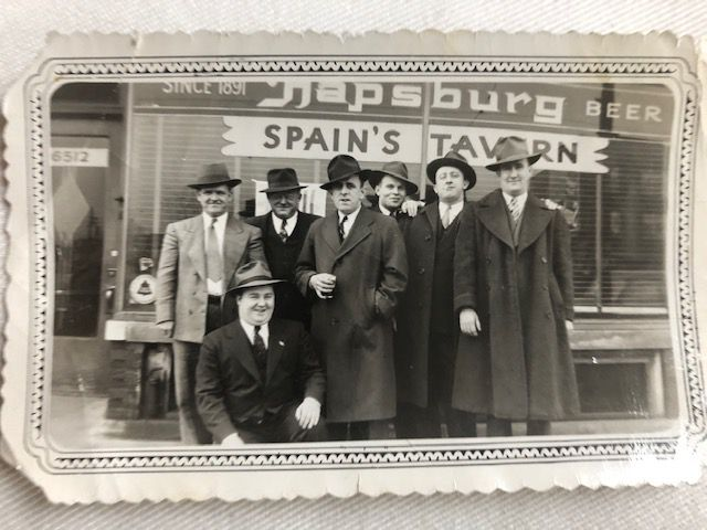 A black and white photo seven men in trench coats wearing fedoras.