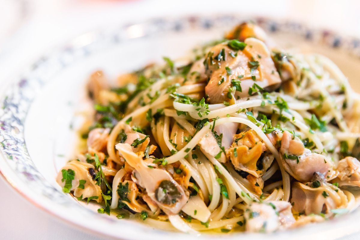 A plate of flat noodles mixed with pink deshelled clams and sprinkled with parsley.