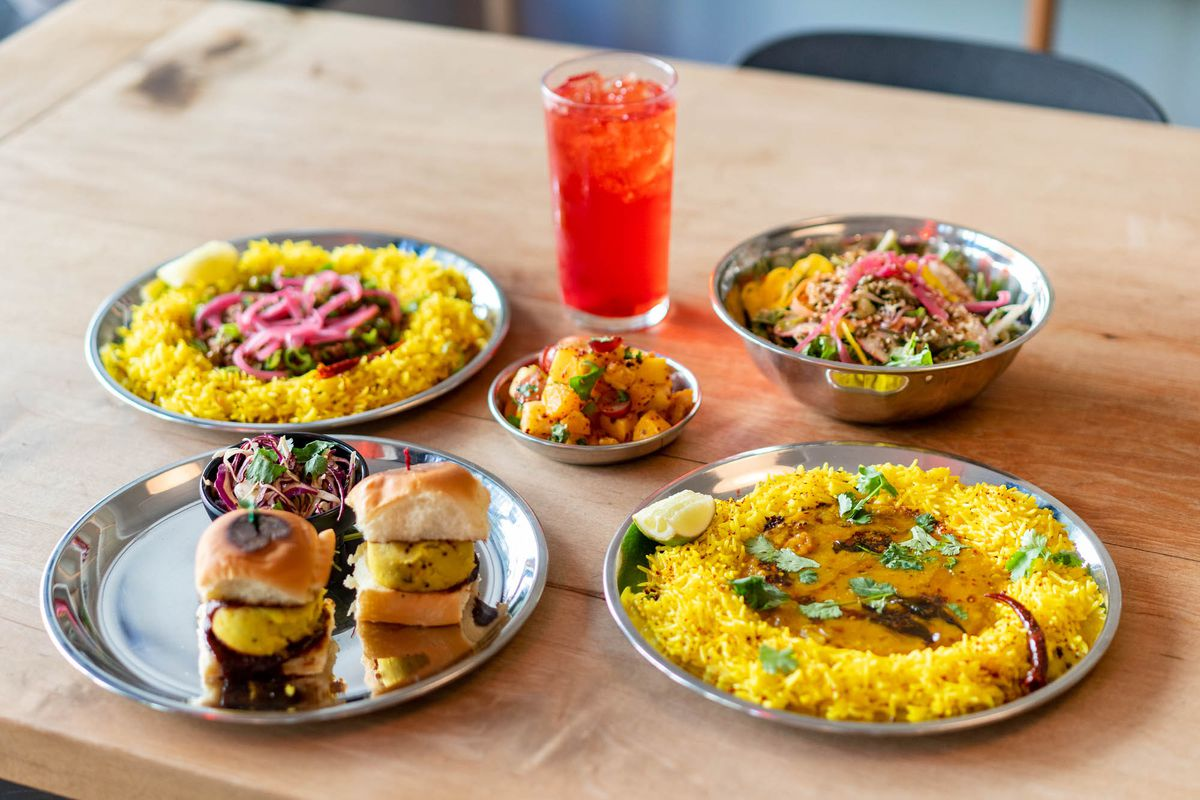 A selection of five silver platters filled with the likes of aloo sliders, kheema, and chana masala, with a light red-colored drink in the center.