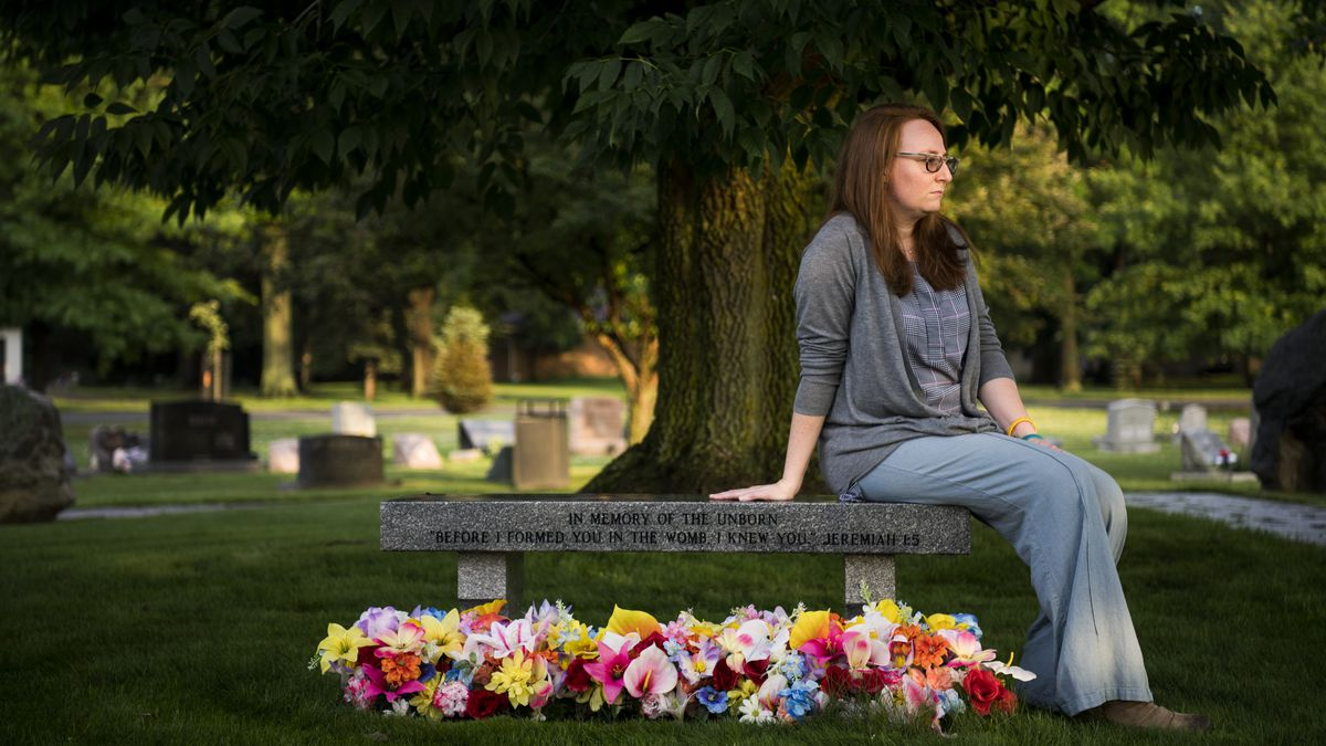 """Kate Plants sits at the memorial bench placed """"in memory of the unborn"""" at the Woodvale Cemetery in Middleburg Heights, Ohio on July 5, 2018. The bench is also in memory of the five embryos she lost to the """"catastrophic failure"""" of a cryotank at the Unive"""