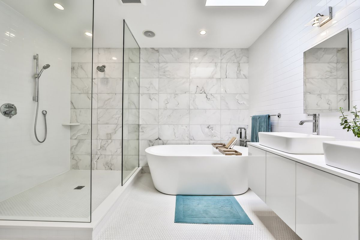 A tub with a blue bath mat, double vanity, glass shower, and white tile.