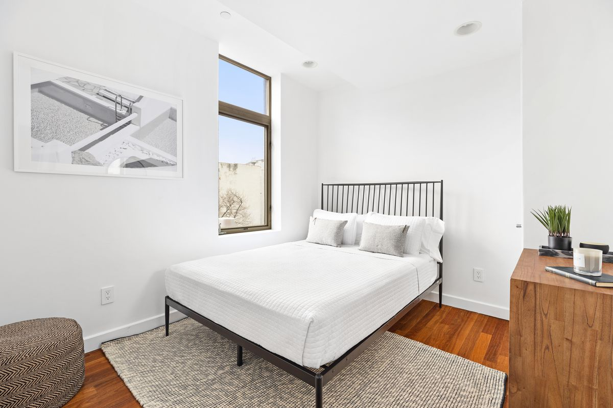 A bedroom with a small bed, hardwood floors, a small window, and white walls.
