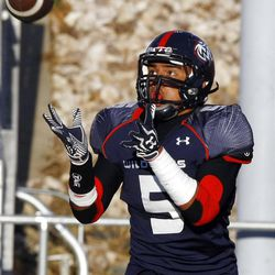 Woods Cross' #5 Filipo Mokofisi reaches up for a ball as he makes a reception for a touch down as they and Mountain Crest play Friday, Aug. 31, 2012.