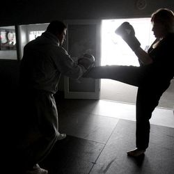 Jeri Hallmand, right, delivers a kick to her trainer Buddy Hudson as the pair work out in a darkened karate gym in Plano, Texas, Wednesday, Feb. 2, 2011. The cold has forced rolling blackouts across Texas.