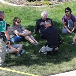A group of residents talk with law enforcement as Sandy police investigate a deadly shooting on Tuesday, June 6, 2017.