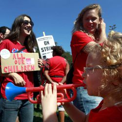 """A young girl plays a toy horn as striking Chicago teachers rally Saturday, Sept. 15, 2012, in Chicago. Union president Karen Lewis reminded that although there is a """"framework"""" for an end to their strike, they still are on strike."""