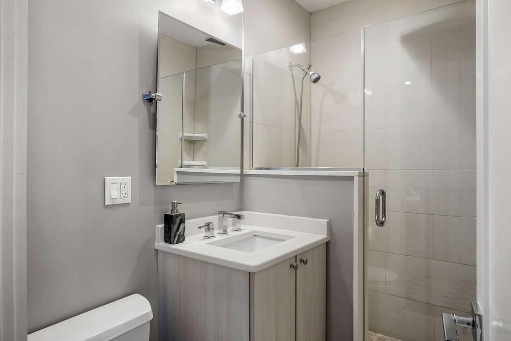 A modern bathroom with the sink next to a glass-door shower.