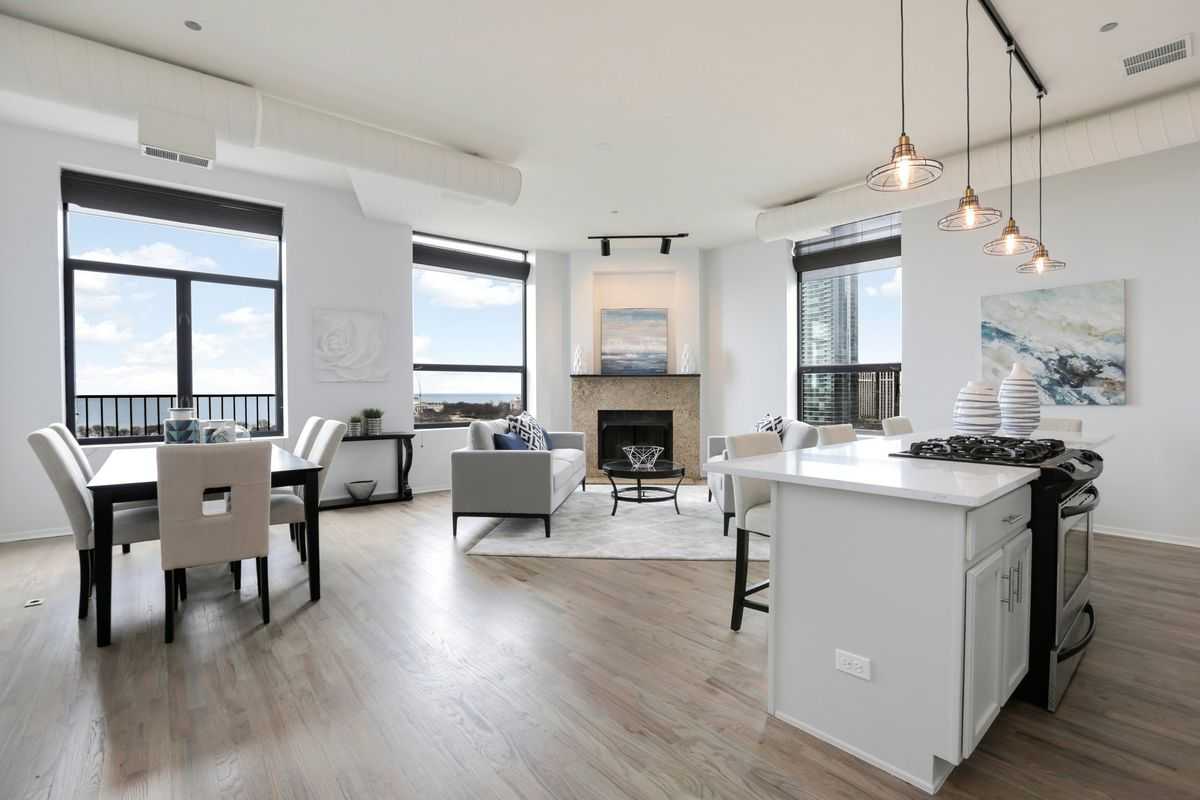 An all-white living and dining area with a corner fireplace and three windows providing views of a large lake.