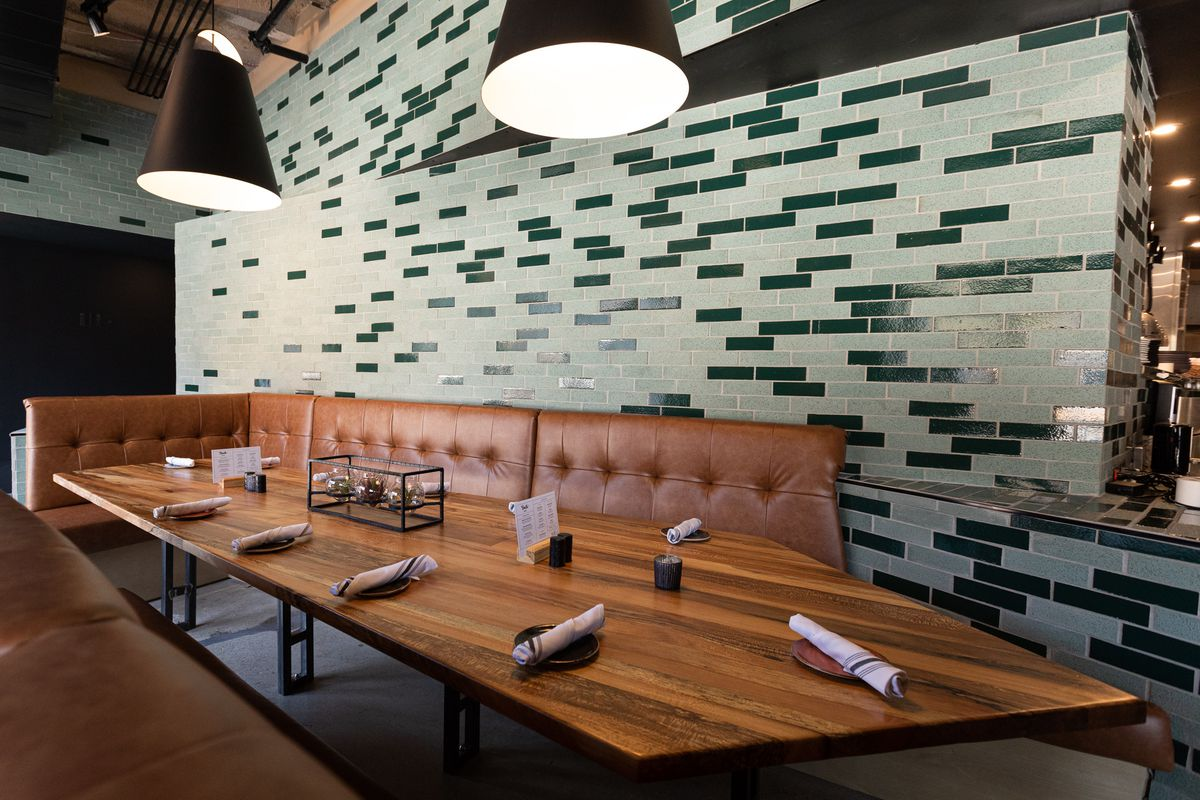A large spear-shaped wooden table surrounded by leather banquettes and light and dark green subway tiled walls.