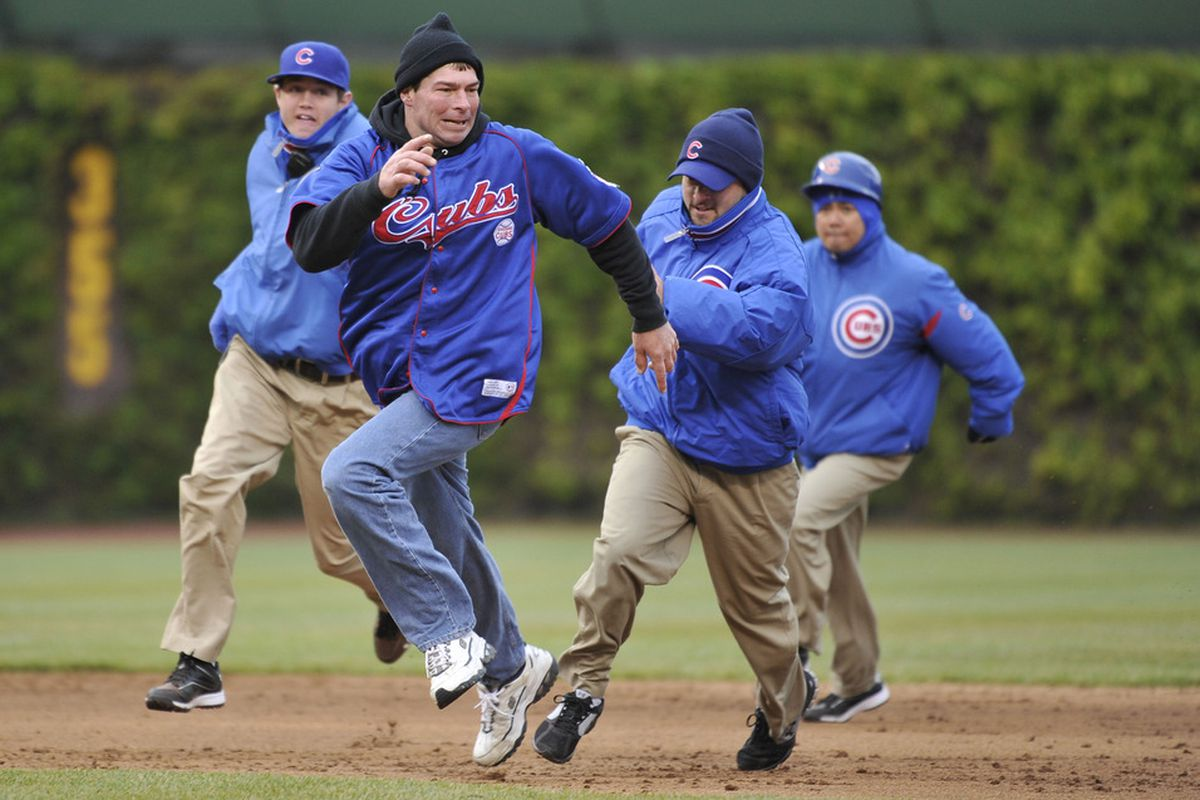 CHICAGO, IL - APRIL 20:   Security personnel chase after a fan who ran on the field during the Chicago Cubs and Cincinnati Reds game at Wrigley Field on April 20, 2012 in Chicago, Illinois.  (Photo by Brian Kersey/Getty Images)