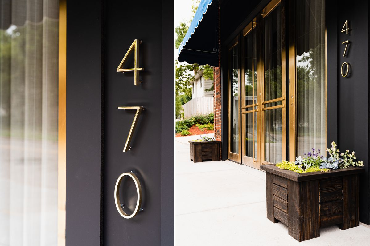 The dark exterior of Myriel with gold address numbers and large art deco doors with gold metal accents