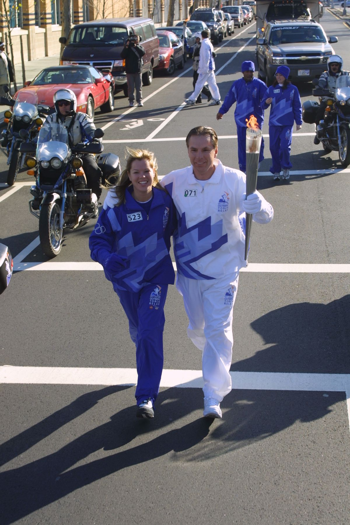 Fraser Bullock, then the chief operating officer of the Salt Lake Organizing Committee for the 2002 Winter Games, and his daughter, Sabrina Gardner, carry the Olympic torch in Staten Island, New York, on Dec. 23, 2001.