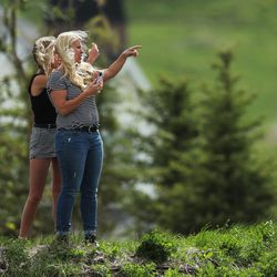 Two women watch as a wildfire burns in the Dutch Hollow area of Midway on Tuesday, May 12, 2020.