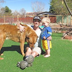 Five years after her miraculous rescue from a remote canyon outside Moab, Nellie Ballengee holds Taz, the faithful dog who saved her, and 18-month-old son William.