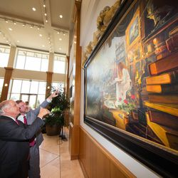 """Leo Beus, front middle, and artist Greg Olsen point to and admire Olsen's latest work, """"Treasures of Knowledge"""" after it was unveiled Wednesday at BYU during Education Week."""