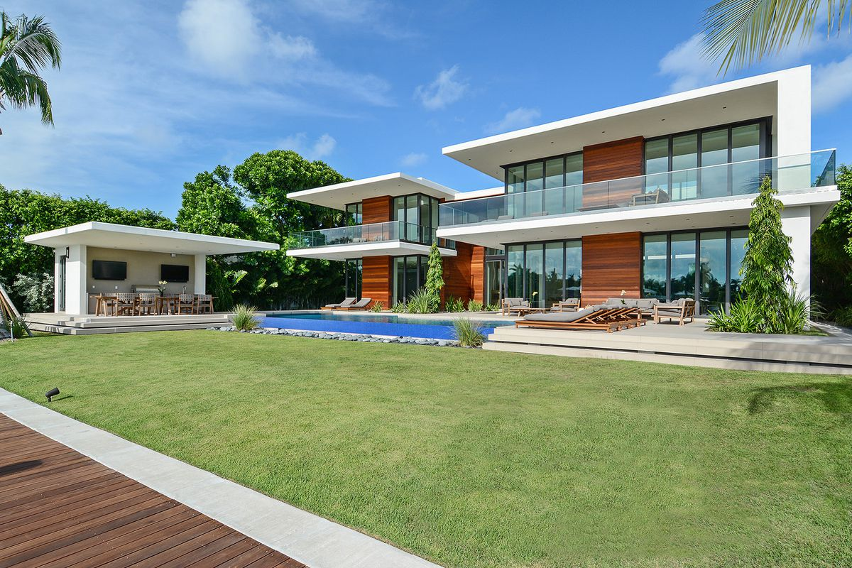 Backyard view of a tropical modern residence on Miami Beach with a blue-tiled infinity edge pool, summer kitchen, and view of the home which features wooden panels and floor-to-ceiling windows.