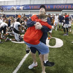 Virginia head football coach, Bronco Mendenhall, gets a huge hug from Thursday's Hero Jerod Davis, at the team's indoor facility after spring NCAA college football practice in Charlottesville, Va., Thursday, April 6, 2017. Thursday's Hero is a program Mendenhall established to honor individuals that have overcome challenges in their lives.