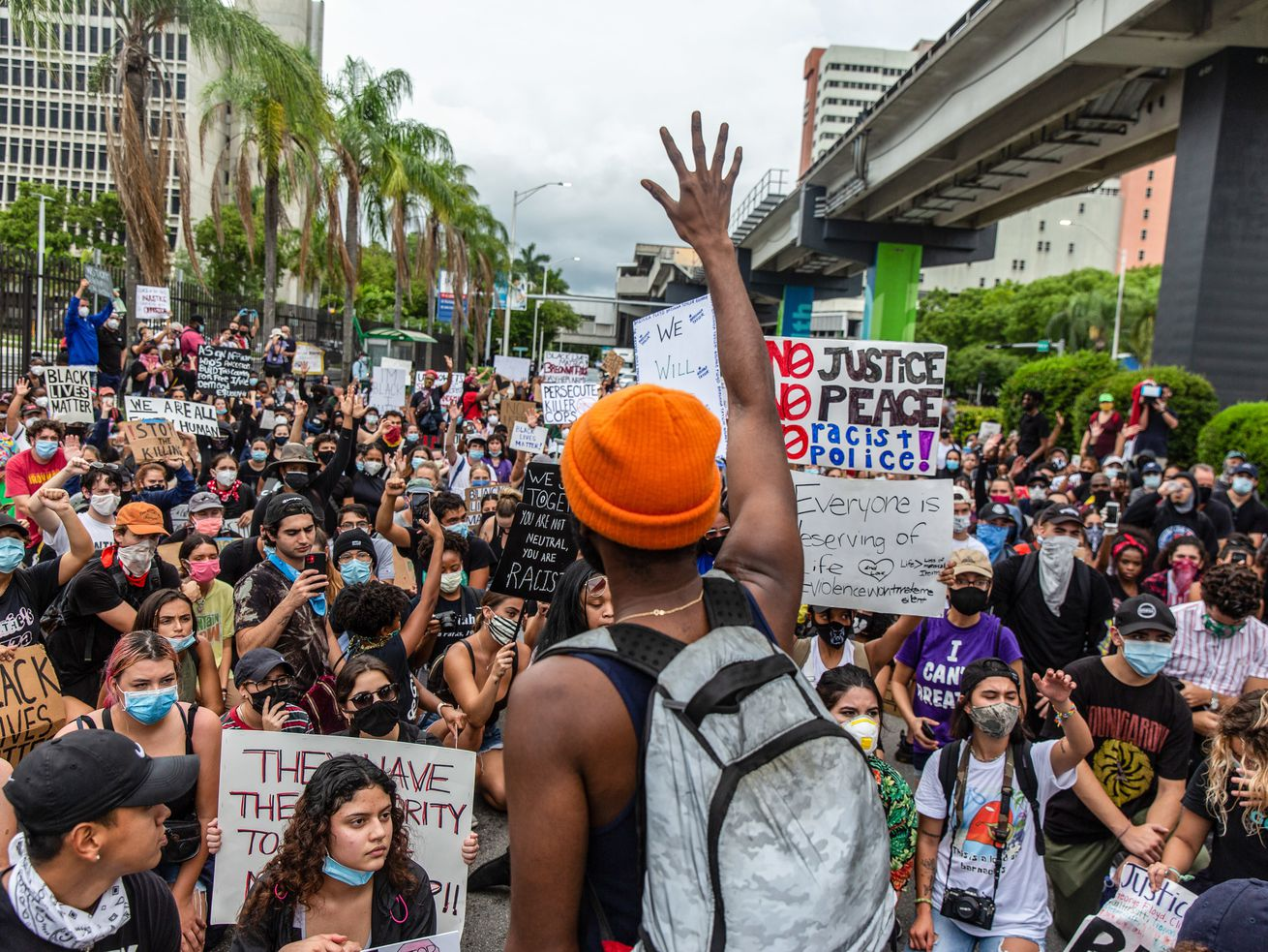 An activist addresses protesters as they march through the...
