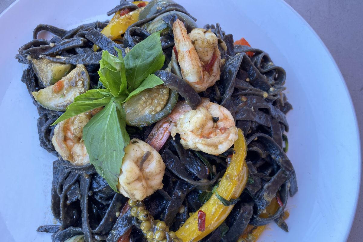 A plate of squid ink noodles comes topped with squash, Thai basil, and peppers at Yui