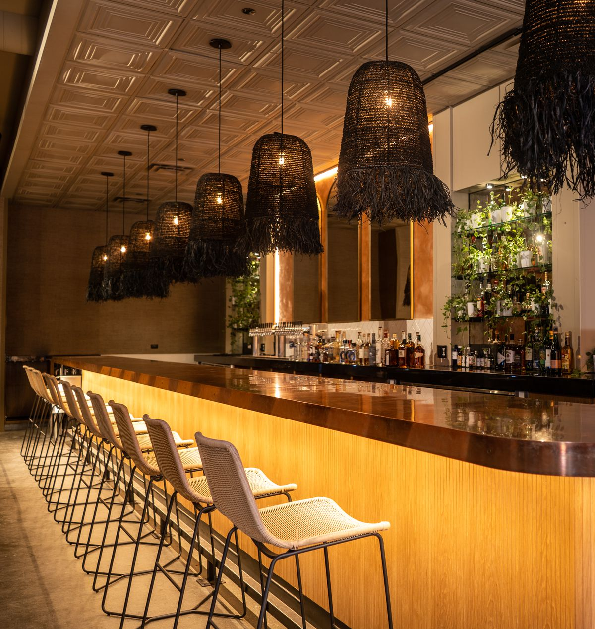 A low-lit natural wood bar with dangling basket lamps overhead