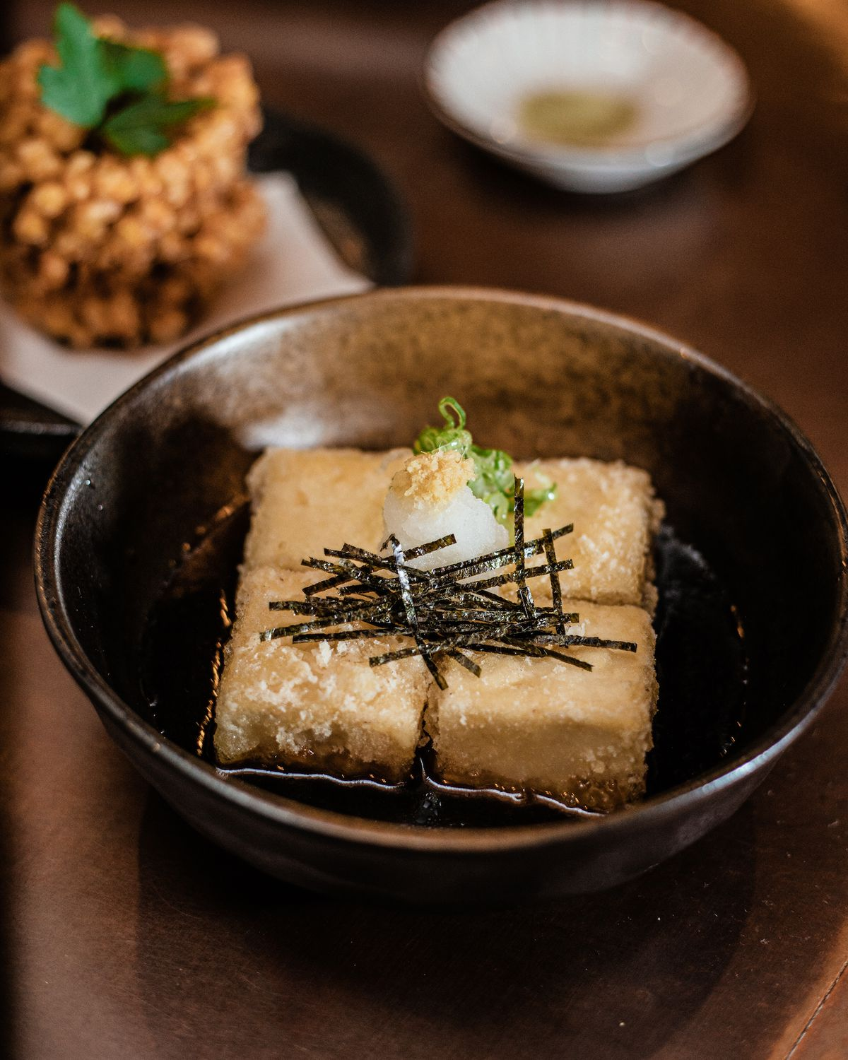 Golden-brown pieces of tofu sit in a black sauce and are topped with pieces of radish and slices of nori.