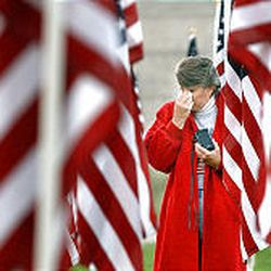 """Lana Barlow walks in Sandy's """"healing field"""" of 3,412 flags after attending Thursday's service at Sandy City Hall. The display honored those who died on 9/11 and soldiers killed in Iraq and Afghanistan."""