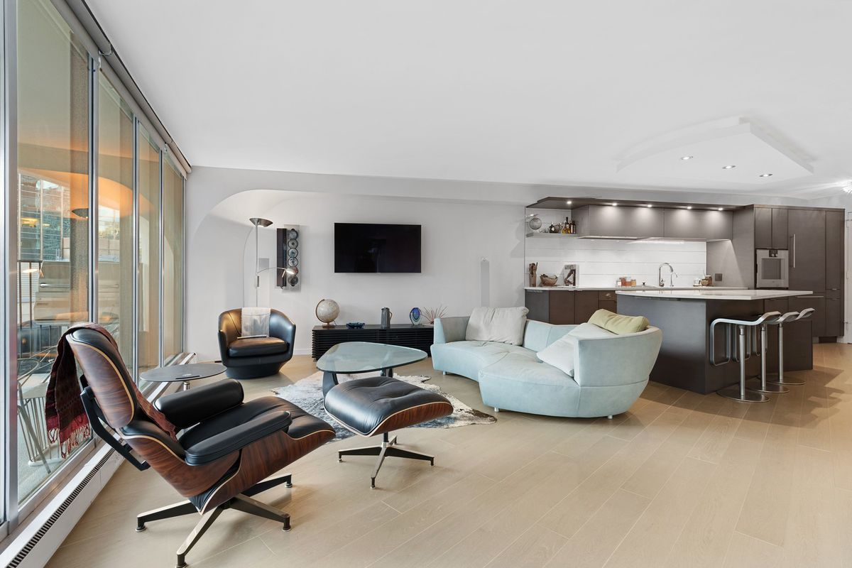 A condo living space with chairs, sofa, table, and floor-to-ceiling glass.