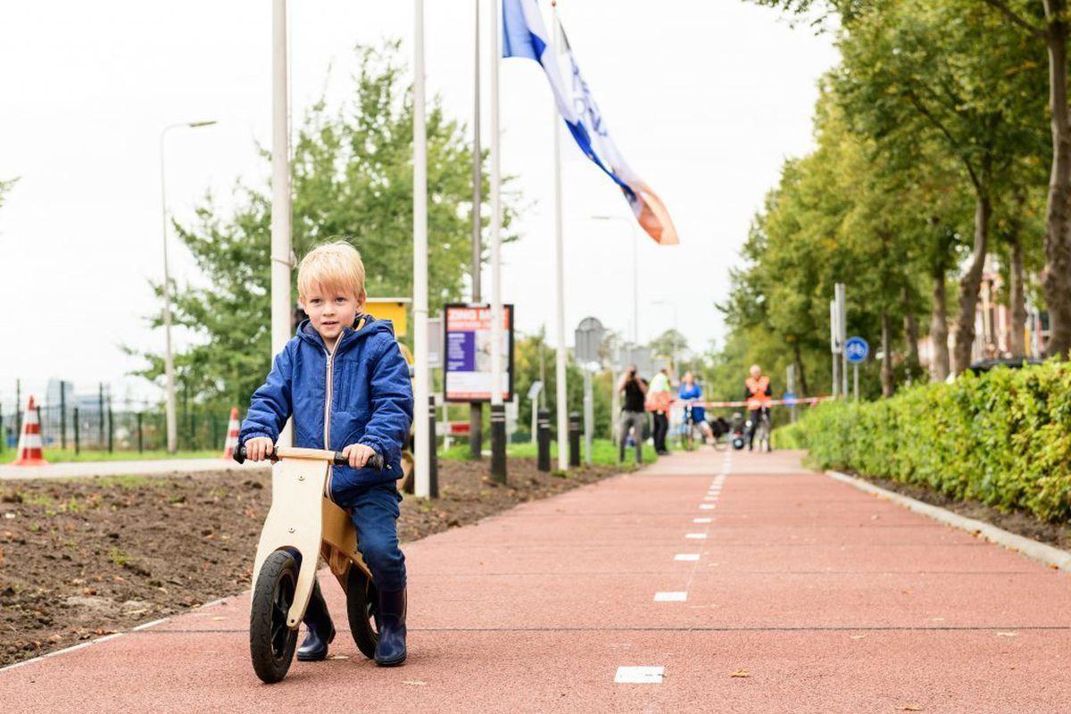 Child riding bike on red bike lane