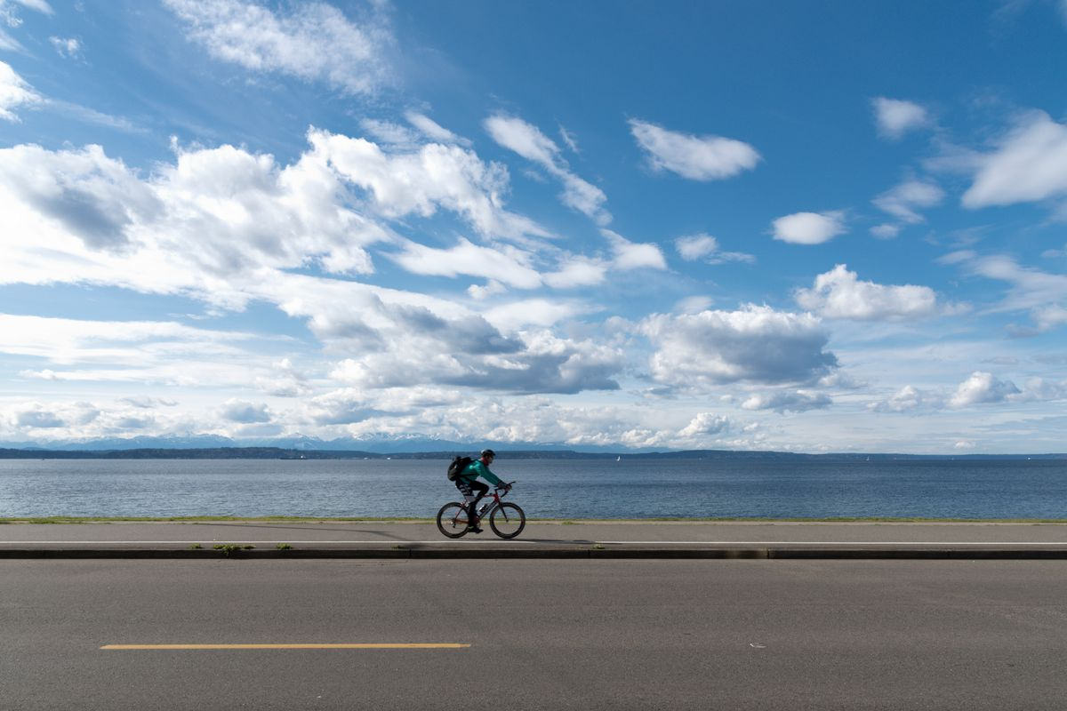 In the foreground is a highway with a bike lane. There is a person riding a bicycle in the bike lane. In the distance is a body of water and a sky with many white clouds.