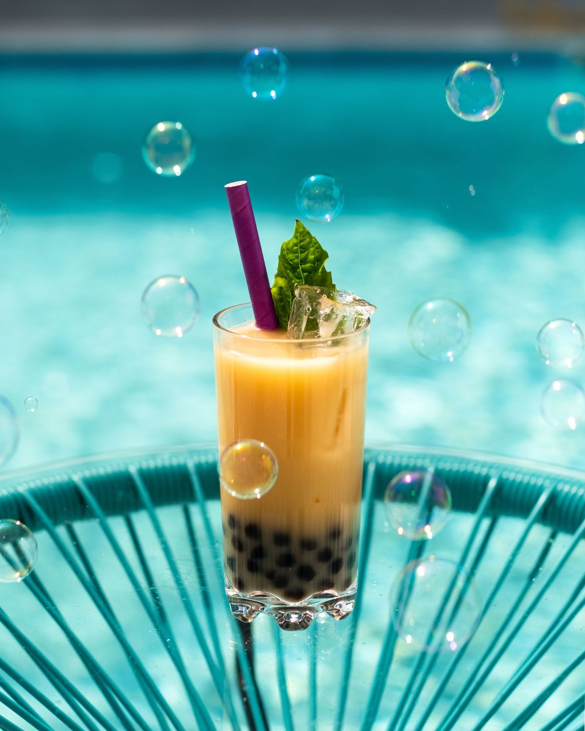 A boba drink on a blue table surronded by bubbles