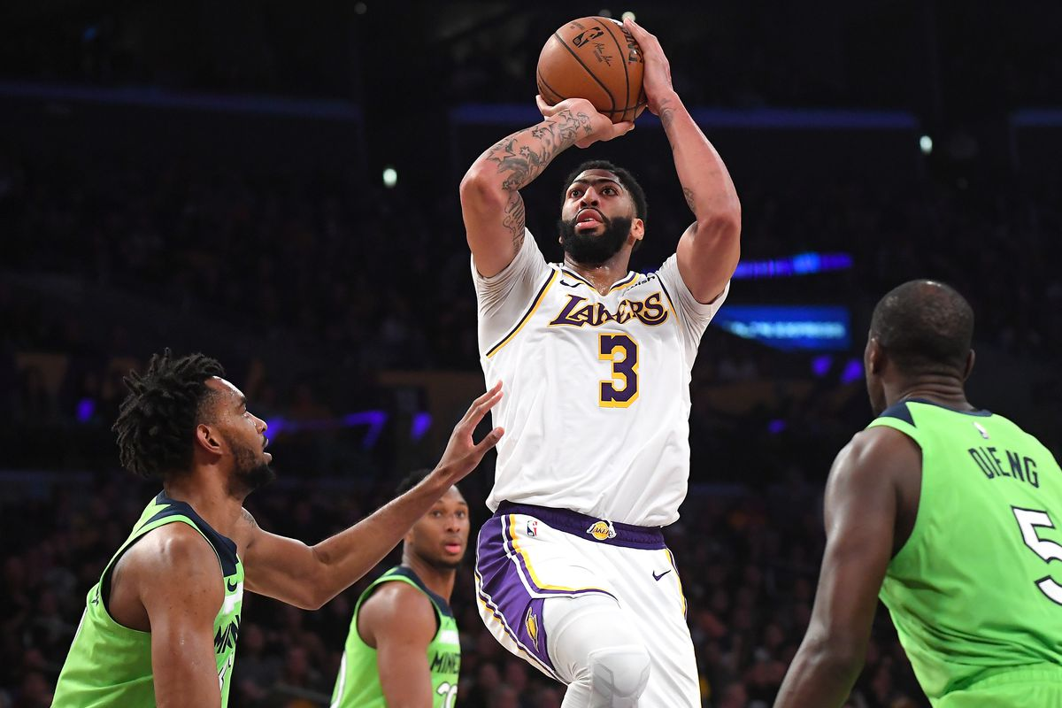 Minnesota Timberwolves forward Keita Bates-Diop and center Gorgui Dieng defend Los Angeles Lakers forward Anthony Davis as he makes a basket in the second half of the game at Staples Center.