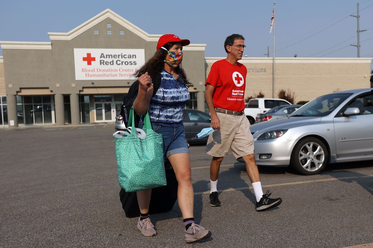 Red Cross volunteer Kay Stevens carries her luggage in Murray on Tuesday, Aug. 31, 2021, as she prepares to go to Louisiana to help with the aftermath of Hurricane Ida. Red Cross volunteer Matt Davidson walks next to her.