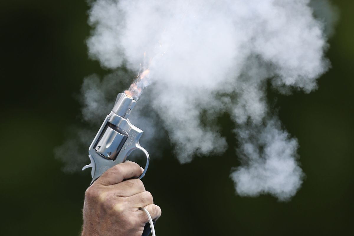 Official Jerry Collet fires the starting pistol during the Utah state boys track meet finals at BYU's track and field complex in Provo on Saturday, May 18, 2019.