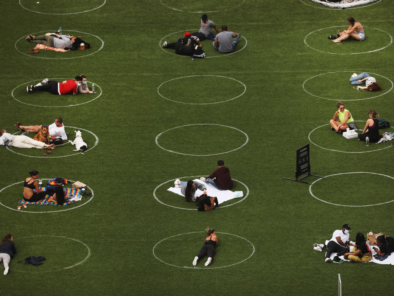 People sit in circles meant to encourage social distancing during the coronavirus pandemic in Domino Park along the East River on May 18, 2020 in the Williamsburg neighborhood of the Brooklyn borough in New York City.