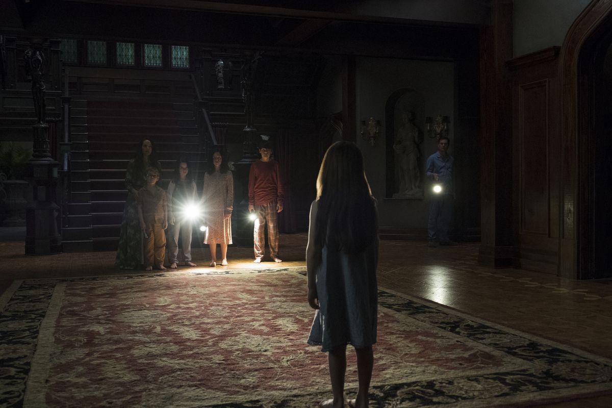 haunting of hill house ghost scene, kids standing in the foyer with flashlights