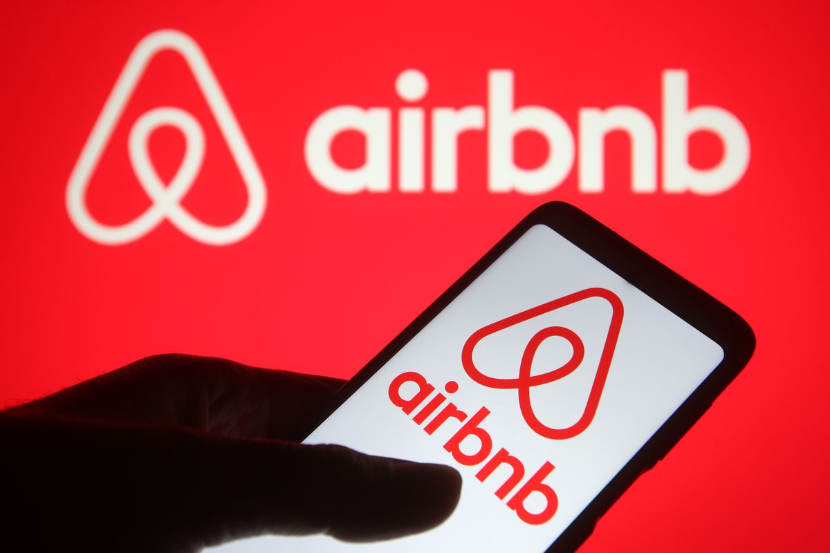 In this photo illustration, an Airbnb logo seen displayed on...