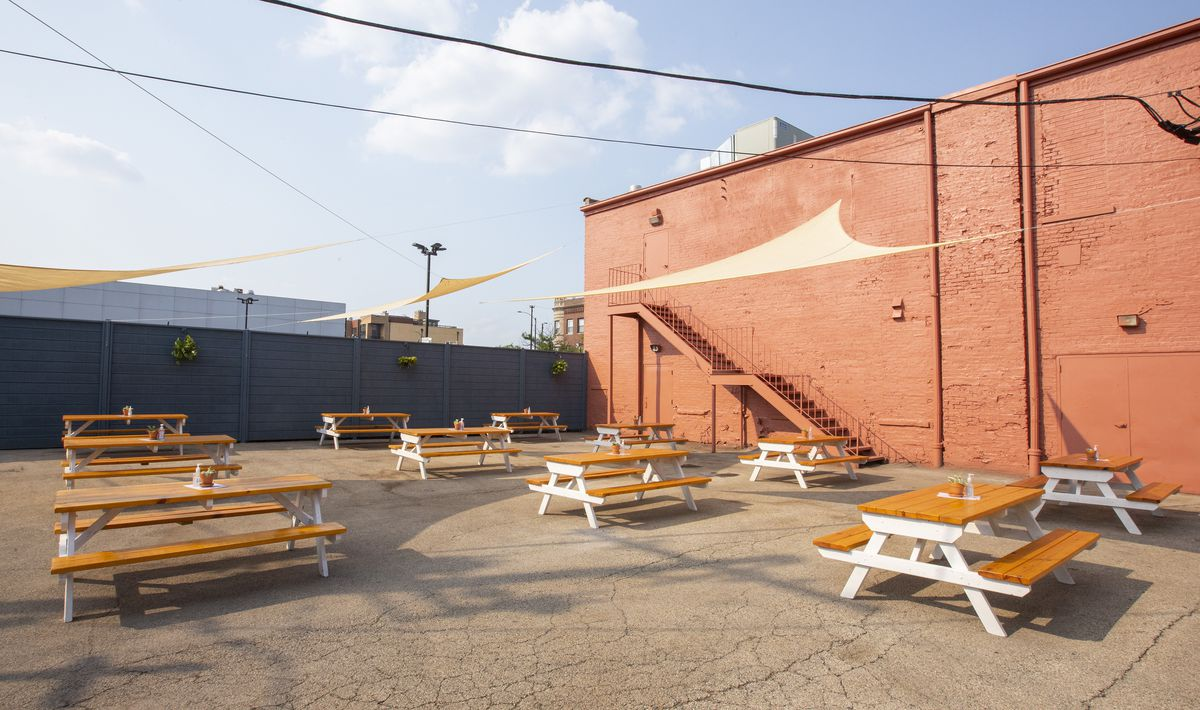 Several picnic tables in an open lot.