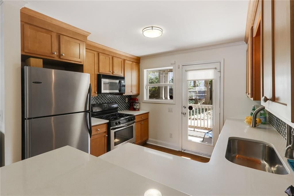 Kitchen with wood cabinets, white countertops, and stainless appliances.