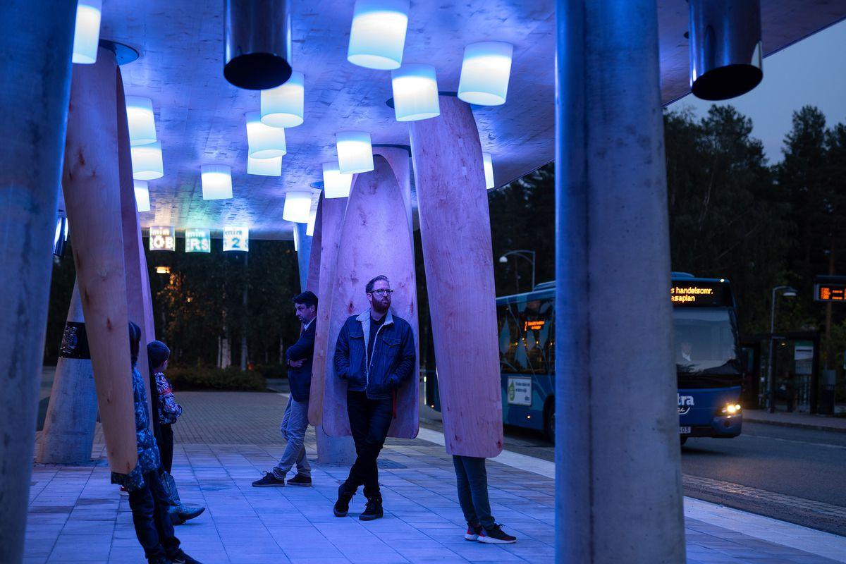 People standing under glowing bust stop.