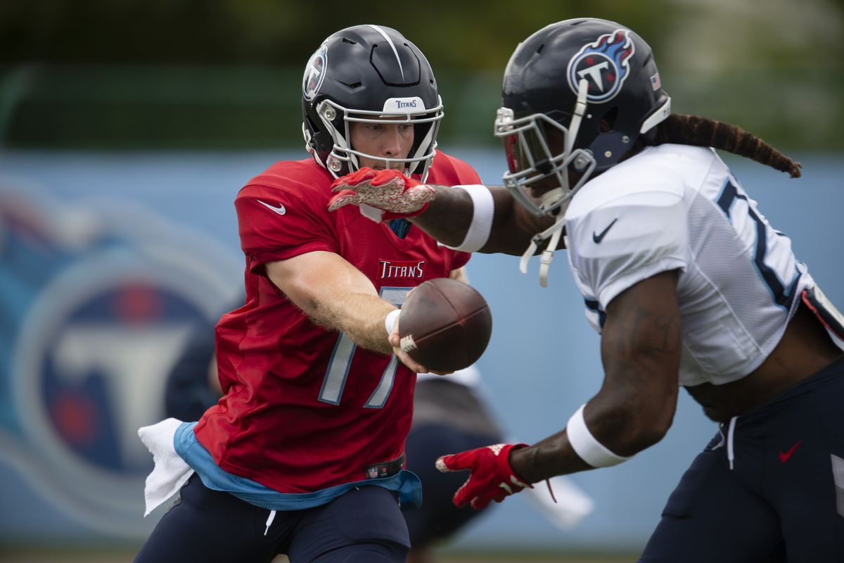 Tennessee Titans quarterback Ryan Tannehill hands the ball off to running back Derrick Henry during practice at Saint Thomas Sports Park.
