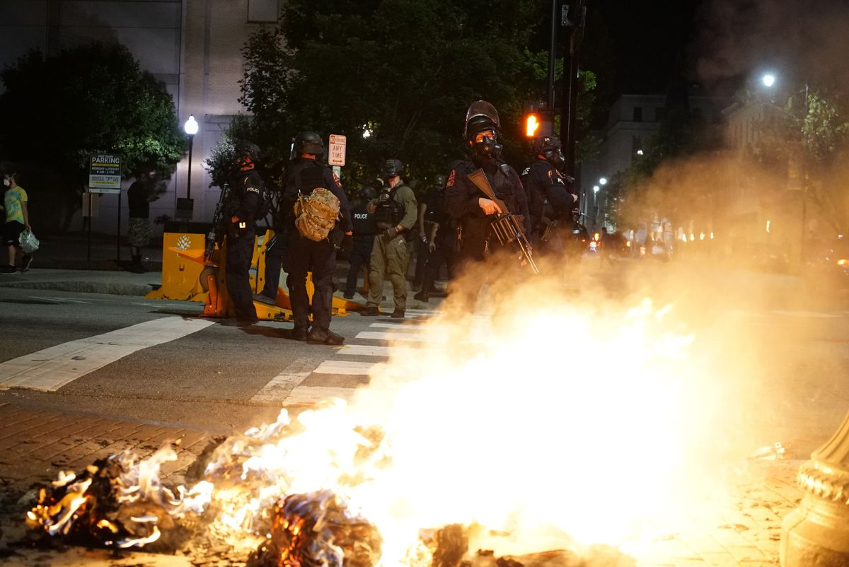 Police stand by as a garbage can burns in Raleigh, N.C., on Sunday, May 31, 2020. It was the second day of protests in the North Carolina capital following the death of Minnesotan George Floyd while in police custody. (AP Photo/Allen G. Breed)