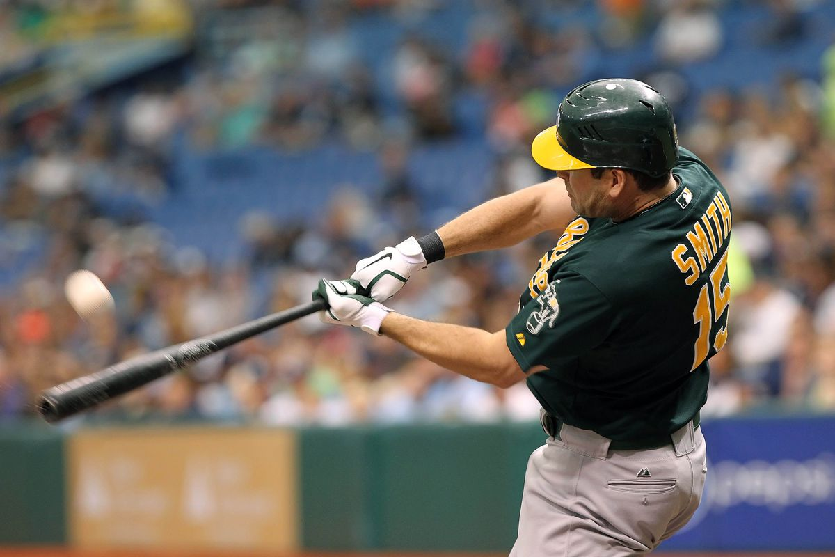 August 25, 2012; St. Petersburg, FL, USA; Oakland Athletics left fielder Seth Smith (15) hits a home run in the third inning against the Tampa Bay Rays at Tropicana Field. Mandatory Credit: Kim Klement-US PRESSWIRE