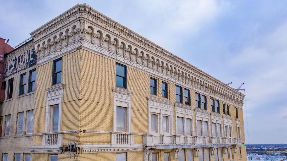 A view of the top two floors plus the decorative cornice. There's a blue sky with a few clouds in the background.