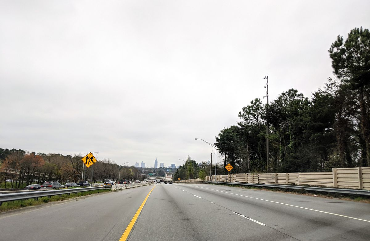 A scene of a roadway in a large city with buildings around, and a few green trees.