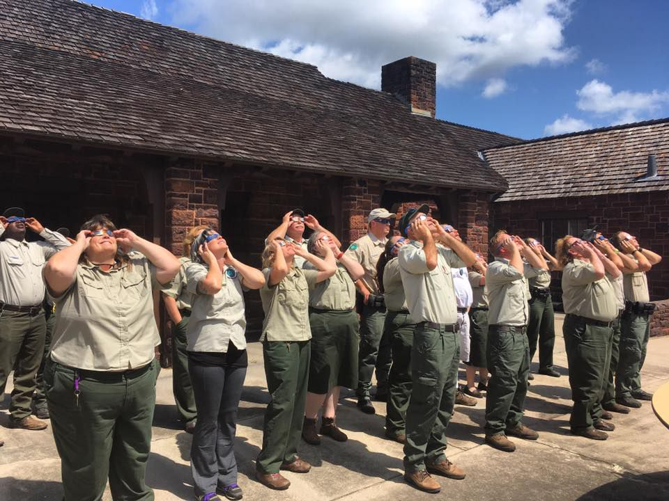 Park rangers in uniform looking at sun through eclipse glasses