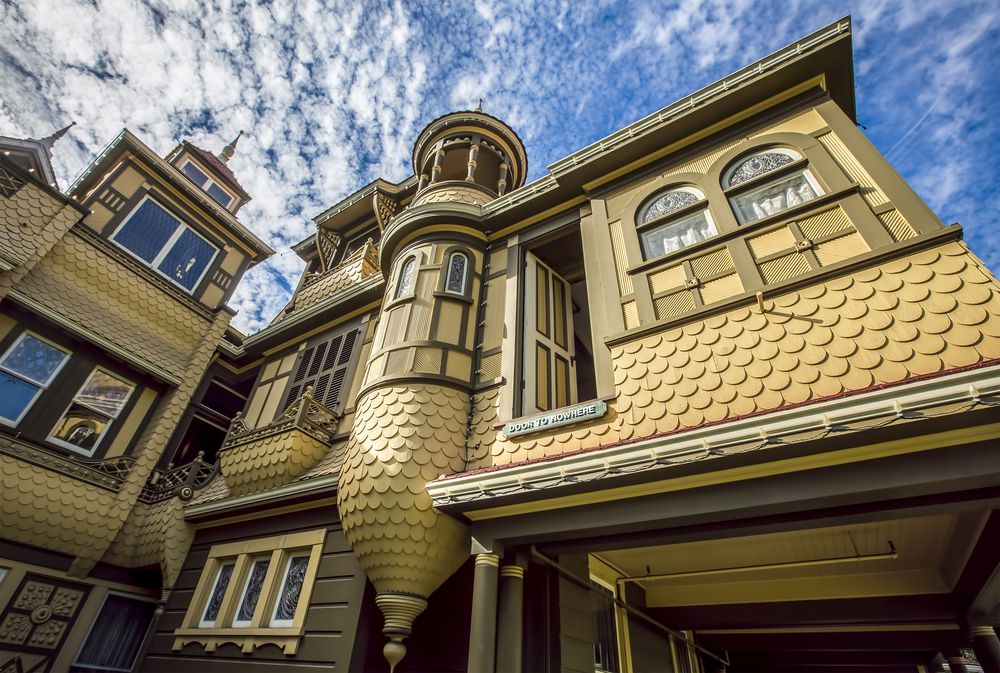A very low angle photo of a yellow Victorian house with shingles, turrets, and multiple windows.