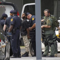 Pittsburgh police place a suspect from a hostage-taking on the 16th floor at Three Gateway Center into a police van on  Friday, Sept. 21, 2012, in Pittsburgh.  Klein Michael Thaxton, 22, surrendered just before 2 p.m., and the man he took hostage was unhurt, Police Chief Nathan Harper said.