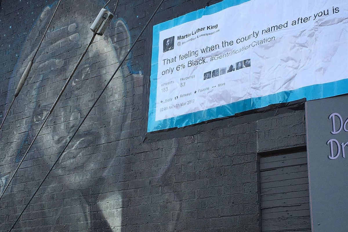 """A mural of Martin Luther King with his head in one of his hands has a printout attached to it in the style of a tweet: """"That feeling when the county named after you is only 6% Black."""""""